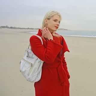 Elischeba Wilde im roten Mantel am Strand in Zeeland