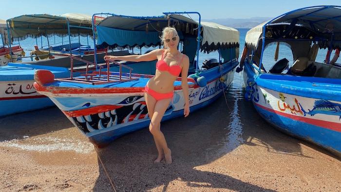 Elischeba im Bikini am Strand von Aqaba in Jordanien vor bunten Booten