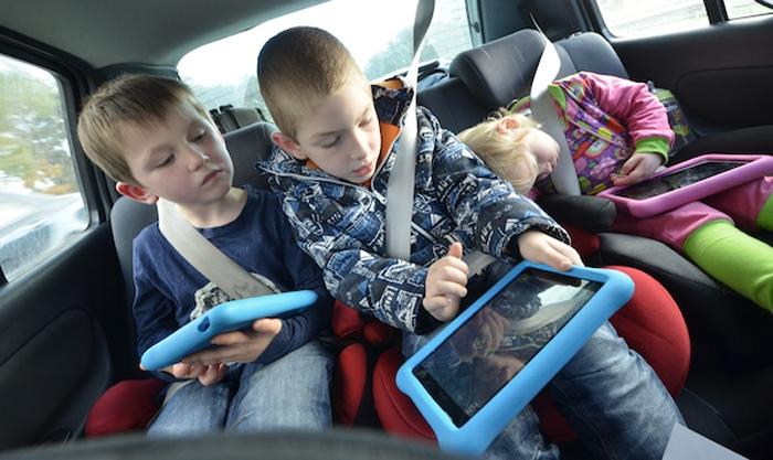 Kinder mit Tablets im Auto