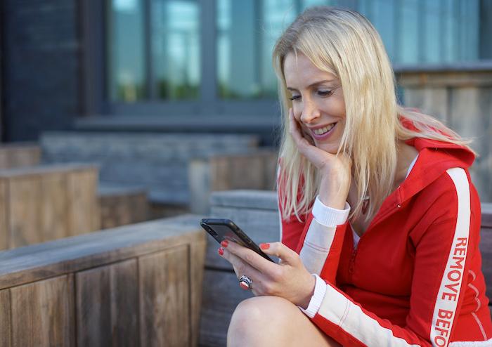 Elischeba Wilde - blonde Frau mit roter Jacke und Smartphone