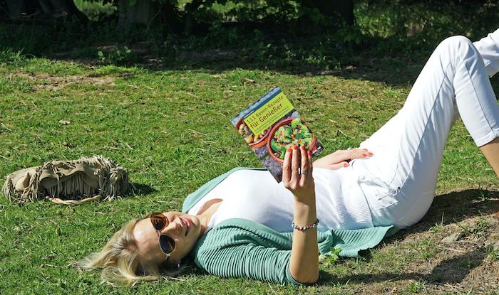 Elischeba Wilde mit Rezeptbuch auf der Wiese liegend