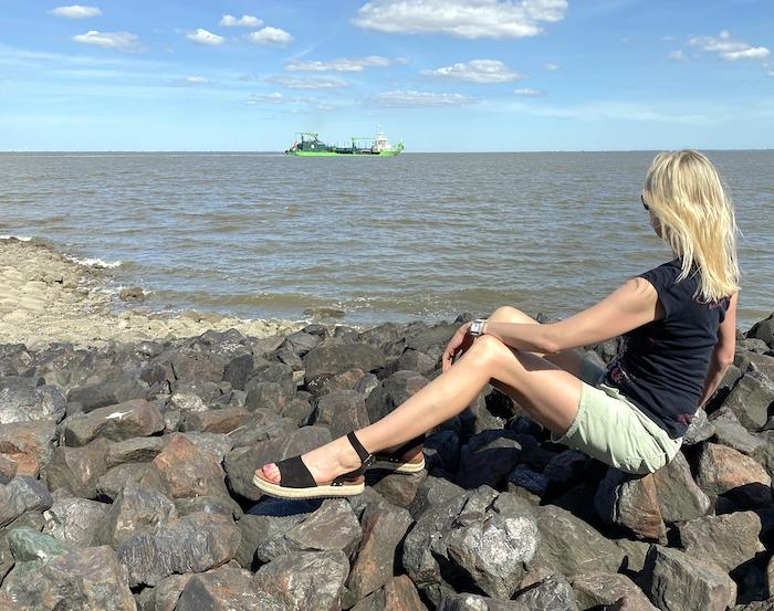 Elischeba Wilde - blonde Frau sitzt auf Steinen und schaut aufs Meer und ein vorbeifahrendes Schiff