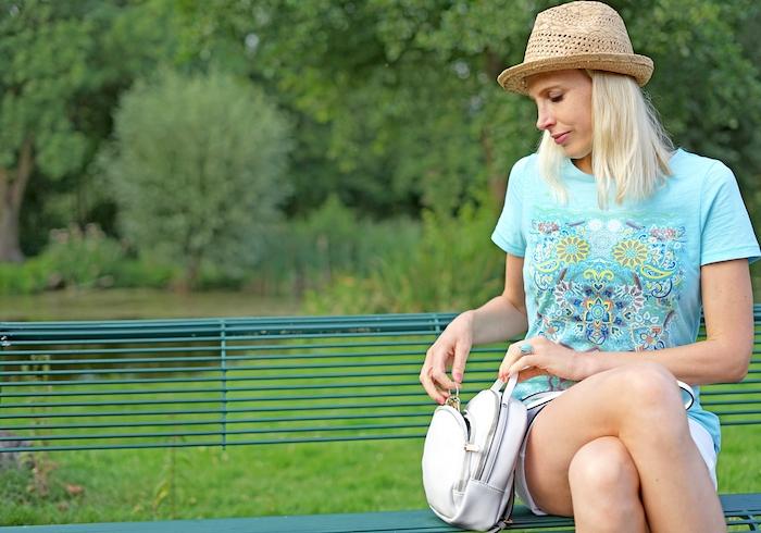Elischeba Wilde - Frau auf der Bank mit weißem Rucksack