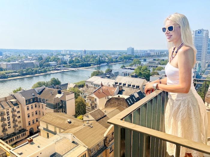 Elischeba Wilde im weißen Kleid mit Sonnenbrille - Blick vom Hotelbalkon auf Frankfurt am Main