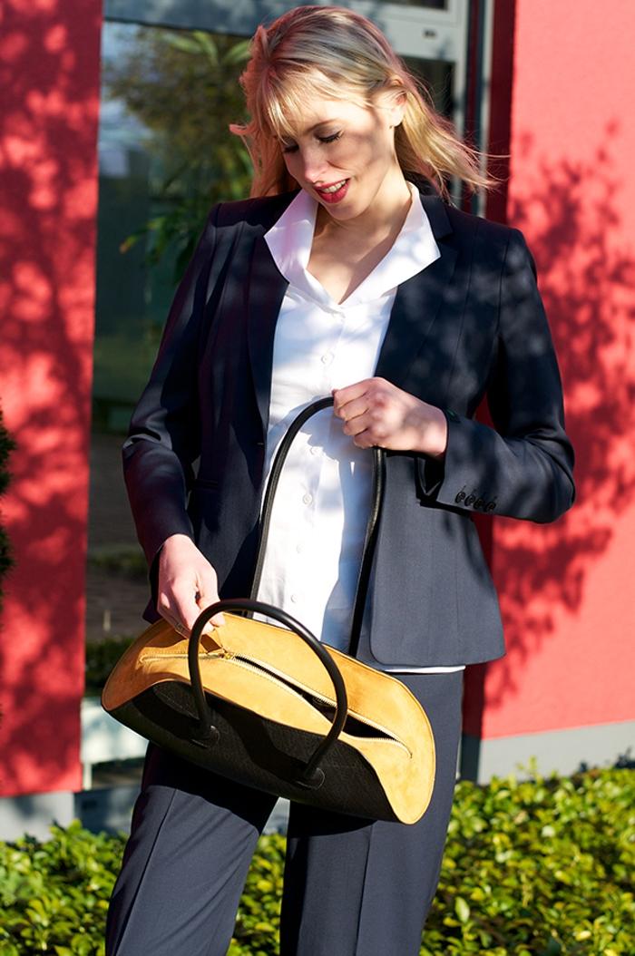 Elischeba Wilde im blauen Hosenanzug mit einer Handtasche von Schreif